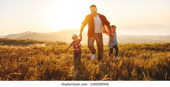 happy family father and children running in nature at sunset