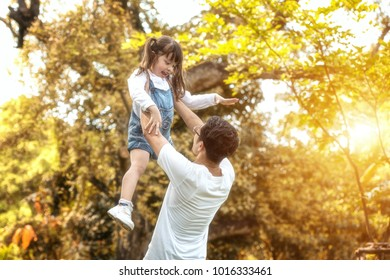 Happy family father and daughter playing together in the garden. Soft focus concept.