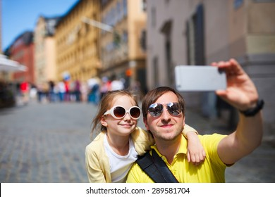 Happy family father and his adorable little daughter taking selfie with mobile phone outdoors at street of Stockholm, Europe