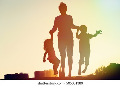 happy family - father with kids jumping from joy at sunset