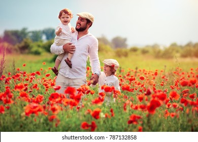 happy family, father with kids playing in poppy flower field at summer day