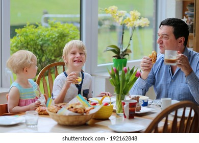 Happy family, father with kids, teenager son and toddler daughter having tasty healthy breakfast eating freshly baked croissants sitting together in sunny kitchen with big garden view window