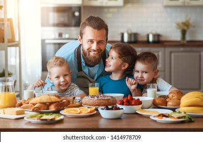 happy family father with many children feeds his sons and daughter in kitchen with Breakfast