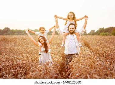 Happy family, father, mom, son and girl in straw hat in wheat field at sunset. The concept of organic farming and healthy lifestyle, healthy food, happiness and joy
