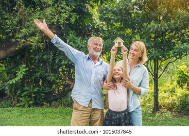 Happy family - father, mother all  children  and holding model house together in park