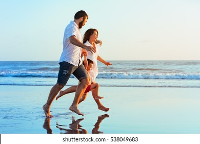 Happy family - father, mother, baby son hold hands, run together with splashes by water pool along sunset sea surf on black sand beach. Travel, active lifestyle, parents with child on summer vacation.