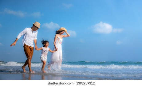 Happy family of father, mother and Daughter relaxing on the beach .Concept for  family holiday ,vacation ,insurance and summer.
