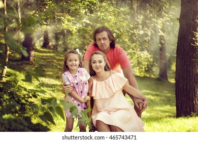 Happy family - father, mother and daughter resting in summer in nature. A woman is pregnant she is sitting on a chair and hugging a girl who laughs