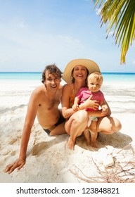 Happy family - father, mother and kid - toddler sitting on the beach