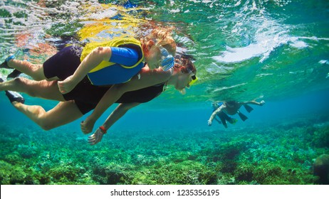 Happy family - father, mother, kids in snorkeling mask dive underwater with tropical fishes in coral reef sea pool. Travel lifestyle, watersport adventure, swimming on summer beach holiday with child.