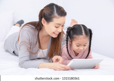 Happy family, Father, Mother, Little child girl using tablet together. Beautiful smiling family lying on bed at home.  Kid family connection education  concept.