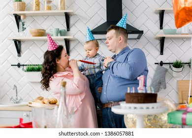 Happy Family, father, mother and little baby boy blowing in party horns on birthday party at home. Portrait of a parents celebrating little their son's first birthday
