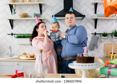 Happy Family, father, mother and little baby boy in party hats blowing in party horns on birthday party at home. Portrait of a parents celebrating little their son's first birthday