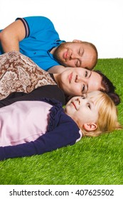 Happy family : father, mother and little daughter lying at green grass isolated in white