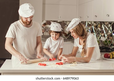 Happy family of father, mother and little son making dough together in the modern white kitchen. Family wearing white aprons and hats.