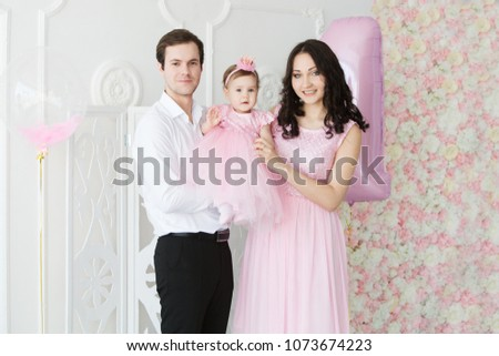 Happy Family Father Mother And One Year Old Child Girl In Pink Dresses