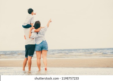 Happy family of father, mother and son goes vacation on a tropical sand beach in summer.