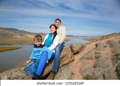 A happy family father and mother and son rest on the mountainside against the backdrop of the valley and river flood plain