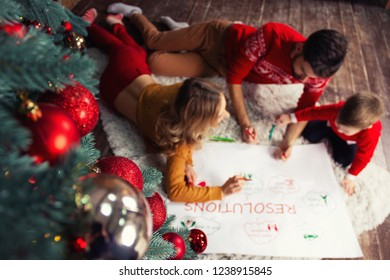 Happy Family: father, mother and son writing future resolutions and plans of family in coming 2019 New Year before night of Christmas Eve and Happy New Year near decorated green Christmas tree.