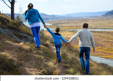 A happy family, father and mother and son, are walking along the slope of the mountains in the direction of the valley below and the floodplain of the river