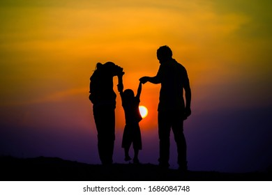 Happy family, father, mother, son in nature, sunset