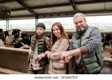 Joyeuse famille de père, mère et fils adolescent en tenue de travail, debout devant la caméra contre de grands paddocks avec des vaches de lait écrémé