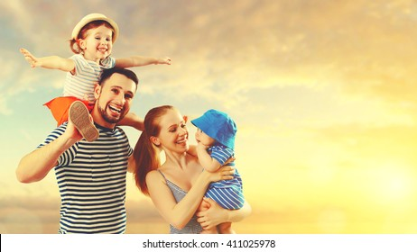 happy family of father, mother and two children, baby son and daughter on  the beach at sunset