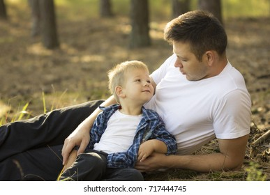 Happy family. Father and son looking at each other  and embracing the outdoors. Father's day