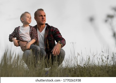 happy family father and son are sitting on the field and watching the sunset. Men's company. Place for text.