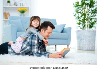 Happy family and father's day concept. Dad with daughter spending time togetherness at home. Cute little girl on dad's back lying on warm floor