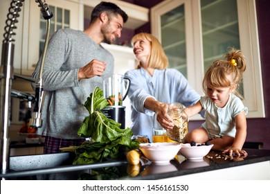 Happy family with female kid having breakfast