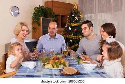 Happy family at festive table near Christmas tree