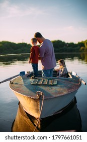 Happy family fishing on boat in summertime. Father teaches son fishing. Back view. Photo for blog about family travel