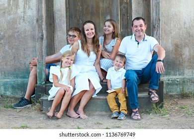 Happy family with five children outdoor near house