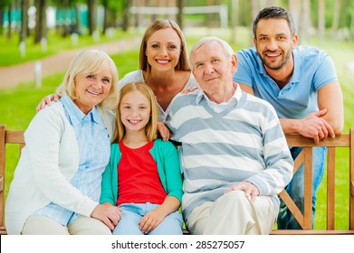 Happy family. Happy family of five people bonding to each other and smiling while sitting outdoors together