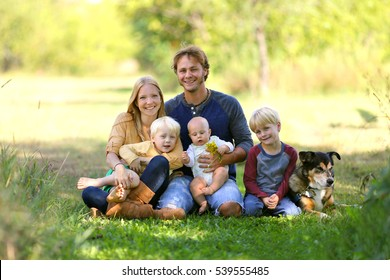 A happy family of five people including mother, father, new baby, boy and his brother are sitting outside in the sunny garden with their adopted German Shepherd dog.