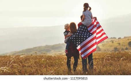 šťastná rodina s vlajkou Ameriky USA při západu slunce venku