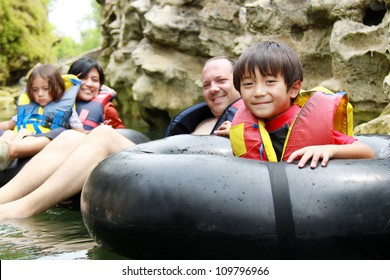 Happy family floating on inflatable tube in river during vacation