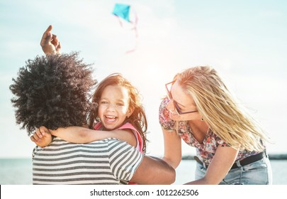 Happy family flying with kite and having fun on the beach - Multi ethnic couple playing with cheerful daughter on weekend vacation - Travel, love, holidays concept - Main focus on mum face