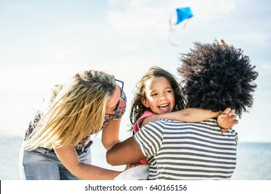 Happy family flying with kite and having fun on the beach - Multi-ethnic couple playing with cheerful daughter on summer vacation - Travel,love,holidays concept - Focus on faces - Warm filter