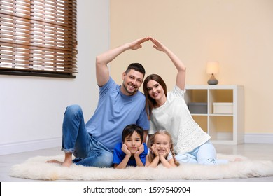 Happy family forming house roof with their hands at home. Insurance concept