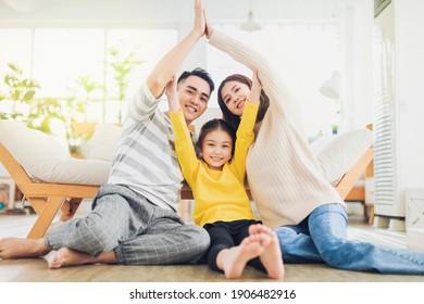 手を家に持って家屋を形成する幸せな家族