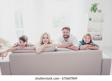 Happy family of four. Blond mom and small girl, brunet dad and little boy, lying on the beige sofa in a row, at home, all cheerful, smiling