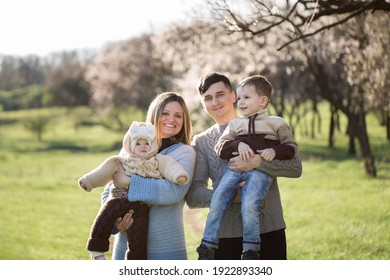 Happy family of four in blooming garden