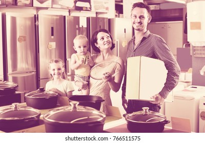 happy family of four buying new cooking pan in household hypermarket