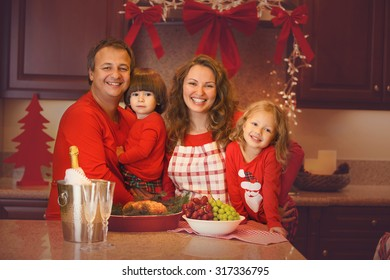 Happy family of four celebrating New Year, Christmas or Thanksgiving day with baked turkey. Mother, father, children with Christmas pajamas.