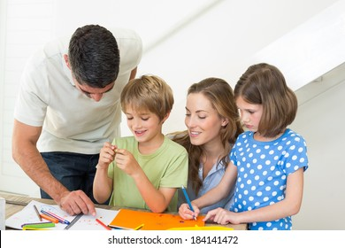 Happy family of four coloring at home