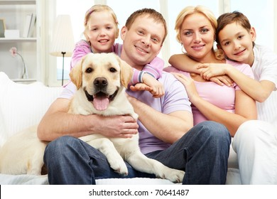 A happy family of four with a dog sitting on sofa, looking at camera and smiling