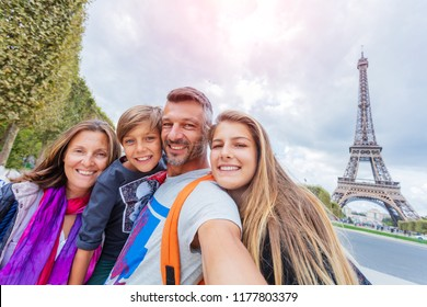 Happy family of four having fun together in Paris near the Eiffel tower