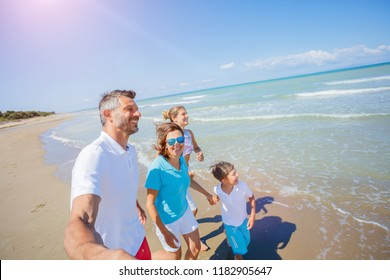 Happy family of four having fun in the summer leisure